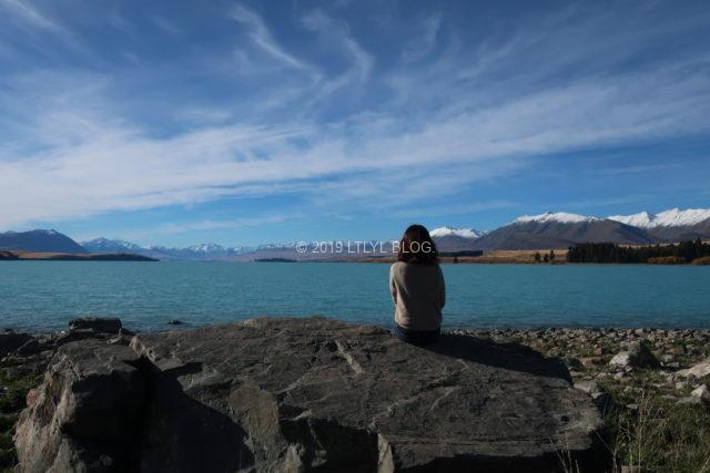 テカポ湖で背中を向けて座る女性