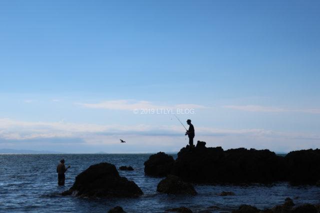 海辺の岩の上から釣りをする男