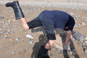 長靴に入った水を捨てるオーナー