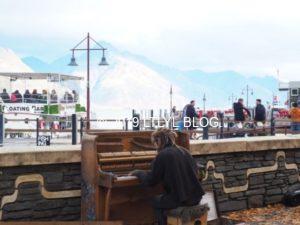クイーンズタウンの港でピアノを弾く男性